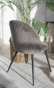 Vista posterior de la silla de terciopelo moderno gris y plantas de interior