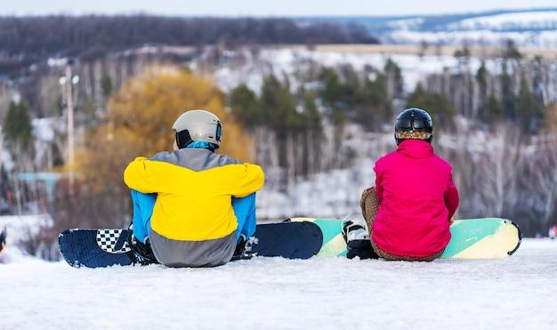 Vista posterior de snowboarders descansando sobre la colina nevada