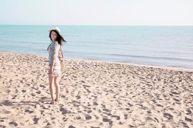 Vista posterior sonriente mujer caminando a la orilla del mar