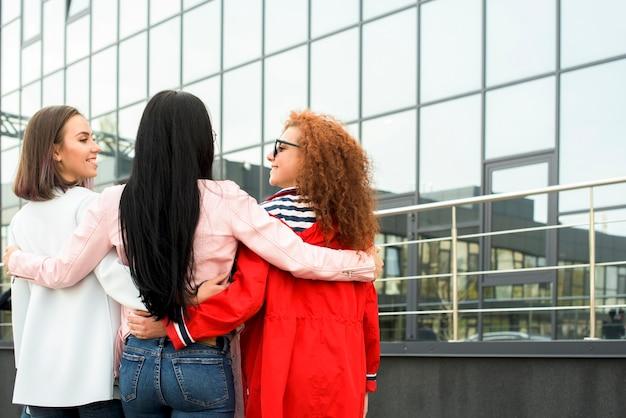 Vista posterior de sonrientes amigas de pie cerca del edificio de cristal