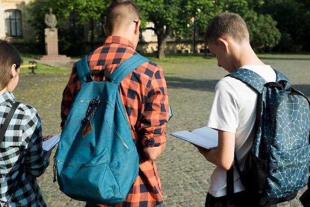 Vista posterior de tiro medio de estudiantes de secundaria leyendo