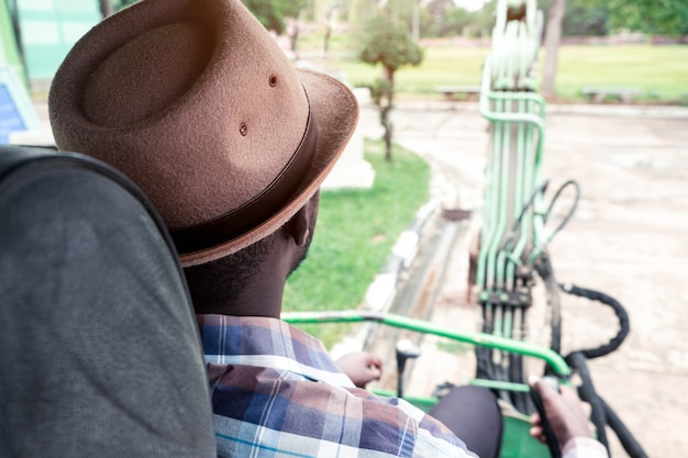 Vista posterior del trabajador africano que conduce la retroexcavadora de equipos de construcción pesada