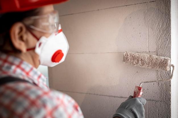 Vista posterior del trabajador de la construcción femenina con casco y rodillo de pintura
