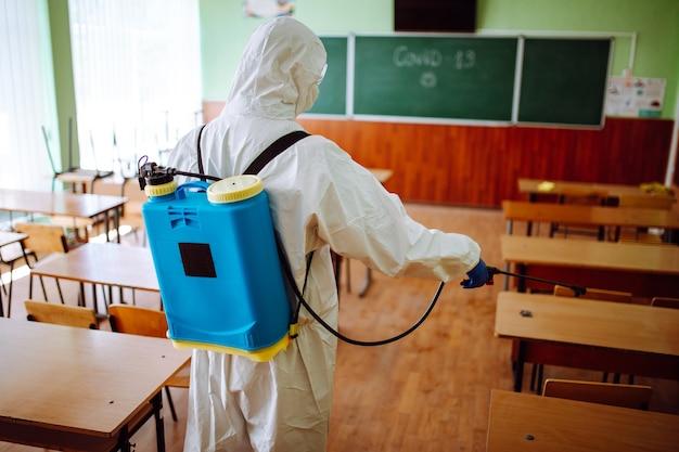Vista posterior de un trabajador sanitario profesional desinfectando el aula antes de que comience el año académico. un hombre con traje protector limpia el auditorio del coronavirus covid-19. cuidado de la salud.