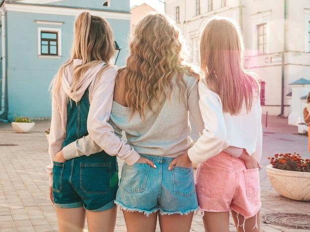 Vista posterior de tres jóvenes amigas hipster. chicas vestidas con ropa casual de verano. mujeres de pie al aire libre. ponen sus manos en pantalones cortos en los bolsillos traseros. posan al atardecer