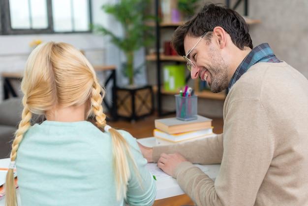 Desde la vista posterior tutor y niña escribiendo