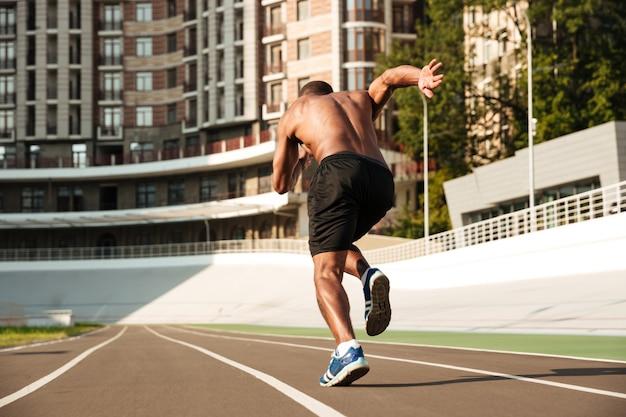Vista posterior del velocista afroamericano que comienza en la pista de atletismo