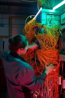 Vista posterior vertical al técnico de red arreglando cables y alambres en la sala de servidores
