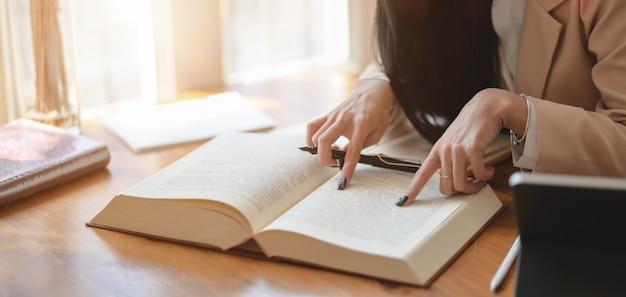Vista de primer plano de una apasionada empresaria trabajando en su proyecto mientras busca información de los libros