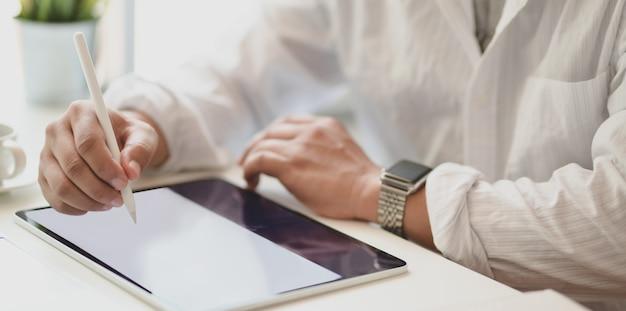 Vista de primer plano del apasionado profesional independiente que planea su concepto de idea en tableta en su oficina moderna