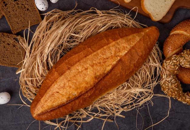Vista de primer plano de baguette en superficie de paja con diferentes panes y huevos sobre fondo marrón