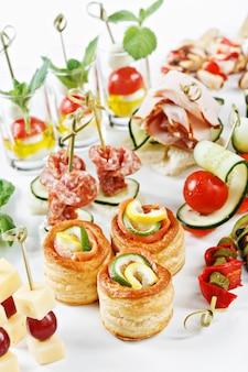 Vista de primer plano conjunto de canapés con verduras, salami, mariscos, carne y decoración en plato blanco