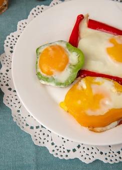 Vista de primer plano del desayuno set plato con huevos y pimientos en papel tapete sobre fondo azul.
