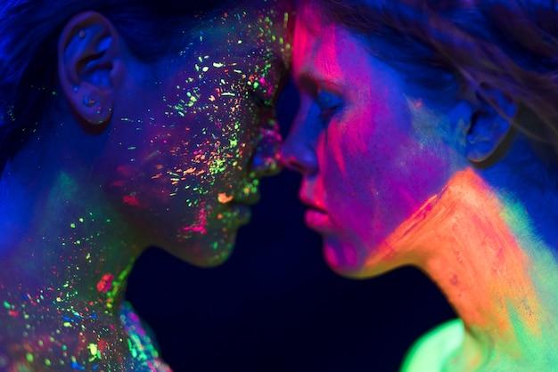 Vista de primer plano de dos personas con maquillaje fluorescente