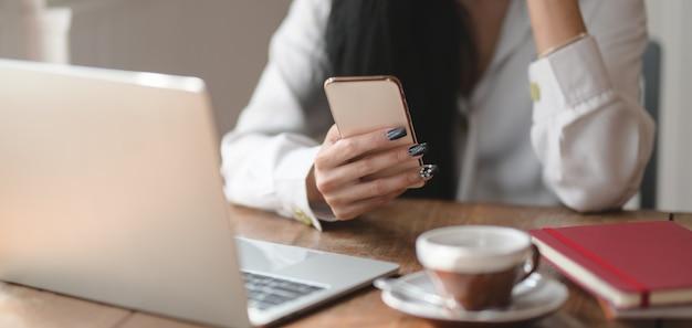 Vista de primer plano de la empresaria que trabaja en su proyecto actual mientras busca información en el teléfono inteligente