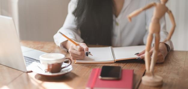 Vista de primer plano de la empresaria que trabaja en su proyecto actual mientras escribe sus conceptos de idea en su cuaderno