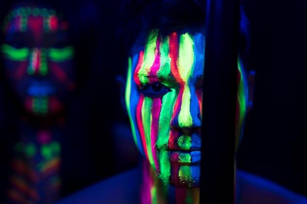 Vista de primer plano del hombre con maquillaje fluorescente y palo