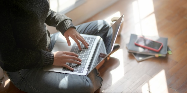 Vista de primer plano de joven profesional independiente trabajando en su proyecto con computadora portátil
