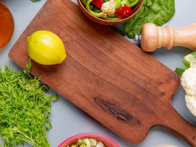 Vista de primer plano de limón en la tabla de cortar con un montón de cilantro en rodajas pimientos col coliflor aceite derretido sobre fondo azul