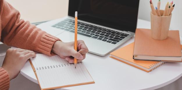 Vista de primer plano de una mujer joven que trabaja en su proyecto mientras redacta su idea en el cuaderno