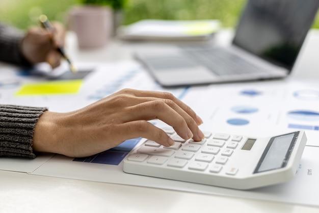 Vista de primer plano una mujer de negocios que usa una calculadora para calcular números en los documentos financieros de una empresa, está analizando datos financieros históricos para planificar cómo hacer crecer la empresa. concepto financiero