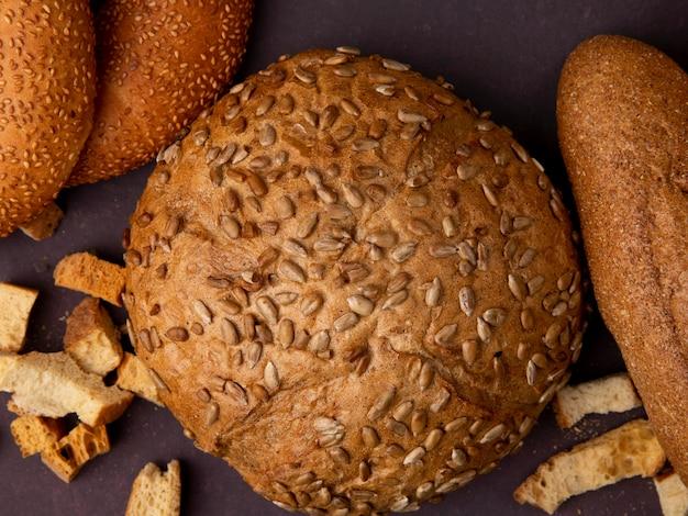 Vista de primer plano de pan de mazorca cutre marrón con bagels y baguette sobre fondo marrón