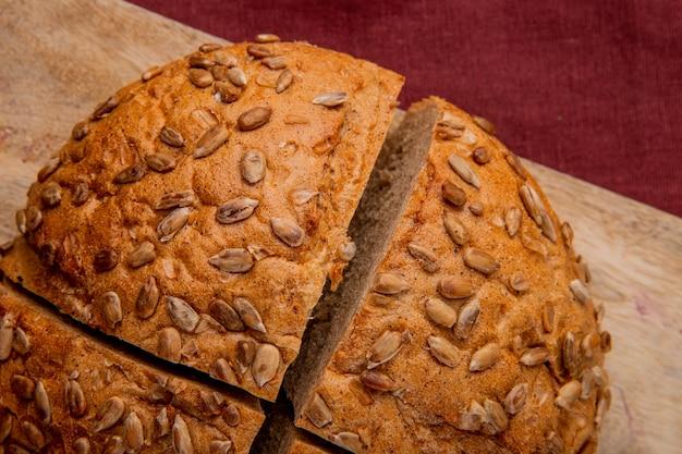 Vista de primer plano de pan negro cortado en superficie de madera y fondo de borgoña