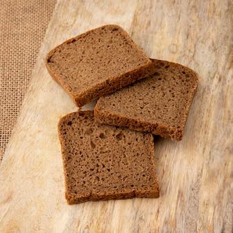 Vista de primer plano de pan negro en rodajas sobre superficie de madera y fondo de tela de saco