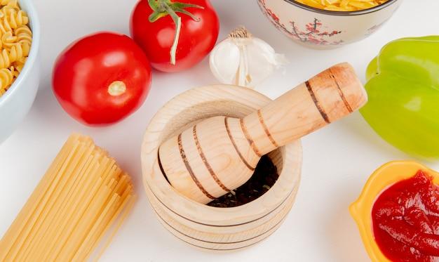 Vista de primer plano de semillas de pimienta negra en trituradora de ajo con macarrones como rotini y fideos de tomate ketchup pimienta de ajo en mesa blanca