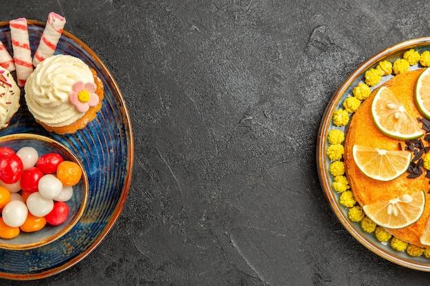 Vista de primer plano superior dulces en el plato apetitosos cupcakes y tazón de dulces junto al pastel con rodajas de frutas cítricas en la mesa negra