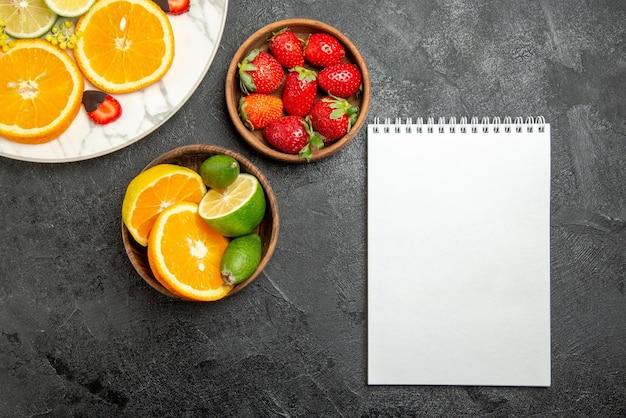 Vista de primer plano superior frutas en tazones de mesa de frutas cítricas y bayas entre plato de fresas cubiertas de chocolate naranja y cuaderno de limón y blanco
