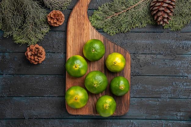 Vista de primer plano superior limones y ramas limones en la tabla de cocina junto a las ramas y los conos de los árboles