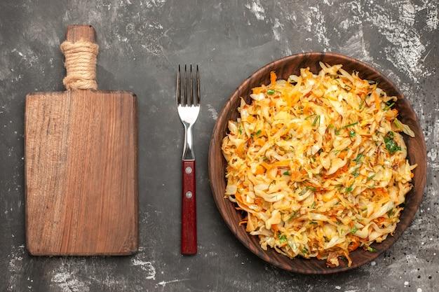 Vista de primer plano superior repollo con zanahorias las apetitosas zanahorias hierbas repollo tablero tenedor