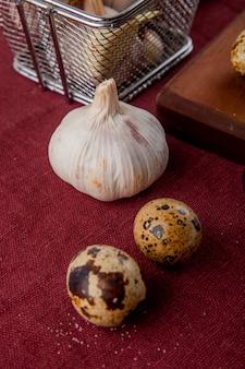 Vista de primer plano de verduras como el ajo y el huevo en el fondo de borgoña