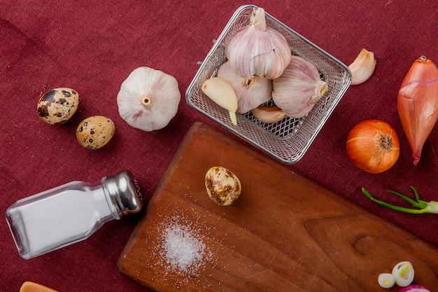 Vista de primer plano de verduras como cebolla de huevo de ajo con sal y tabla de cortar sobre fondo burdeos