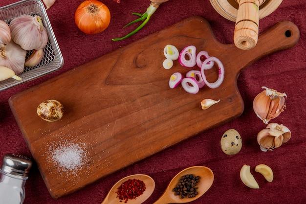 Vista de primer plano de verduras como huevo de cebolla en tabla de cortar ajo con sal y especias sobre fondo de borgoña
