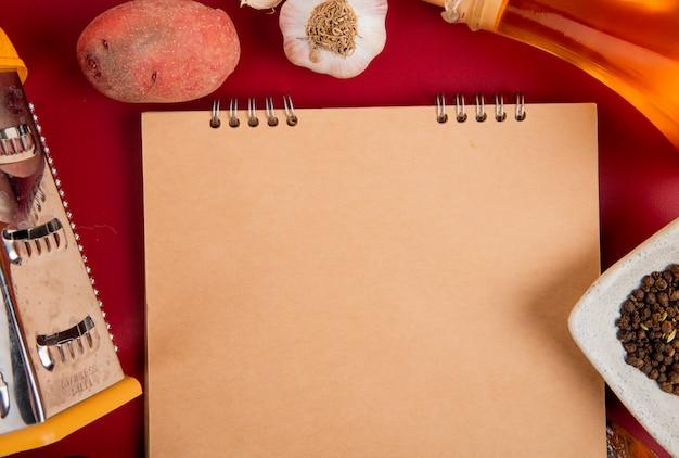 Vista de primer plano de verduras como patata y ajo con mantequilla, pimienta negra y rallador alrededor del bloc de notas en el fondo bordo con espacio de copia