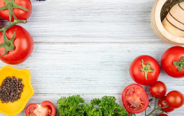 Vista de primer plano de verduras como tomate cilantro con pimienta negra trituradora de ajo en mesa de madera con espacio de copia