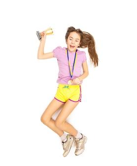 Vista desde el punto más alto de la niña animando saltando alto con medalla de oro y copa