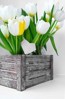 Vista de un ramo de tulipanes blancos de pie en una caja de madera