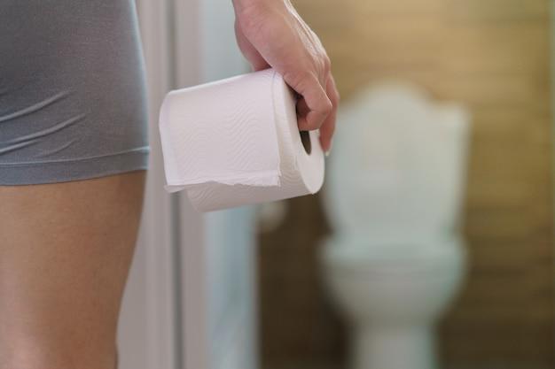 Vista rara del hombre que sostiene el rollo de papel higiénico en la parte delantera del inodoro.