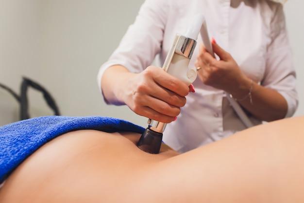 Vista recortada de cosmetóloga con rodillo haciendo nalgas masaje starvac.