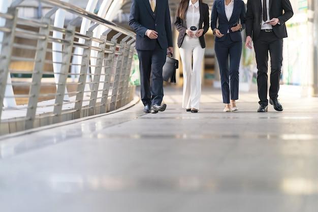 Vista recortada de cuatro ejecutivos seguidos, un grupo de cuatro empresarios caminando y hablando entre sí