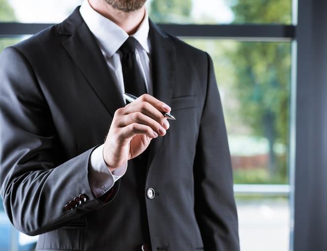 Vista recortada del empresario en traje de cantar algo en la oficina