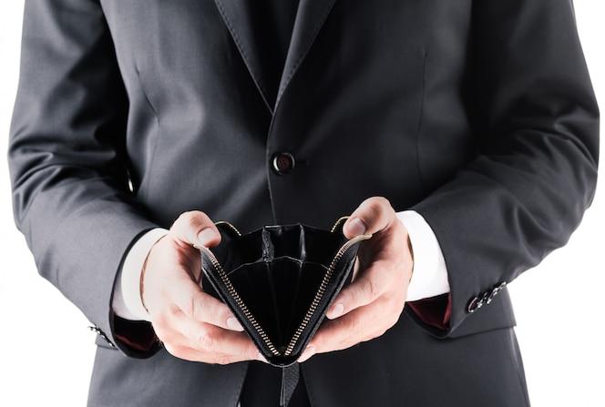 Vista recortada del empresario en traje negro con billetera vacía, aislado en blanco