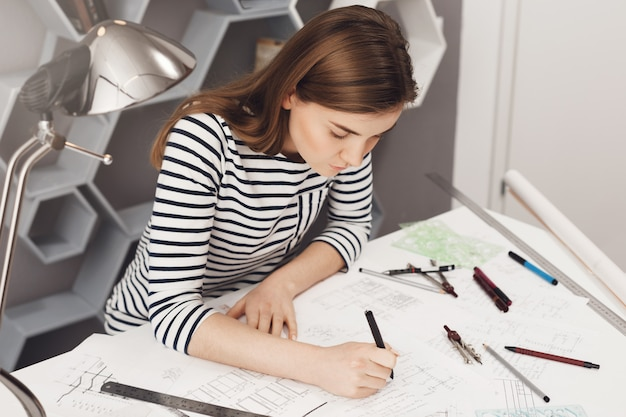 Vista recortada de la joven ingeniera independiente europea con ropa de rayas no formales, sentada a la mesa en un cómodo espacio de coworking, haciendo su trabajo, usando muchos artículos de papelería.