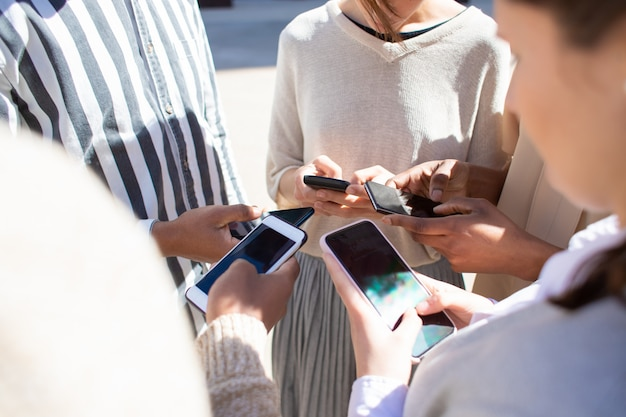 Vista recortada de jóvenes que usan teléfonos inteligentes