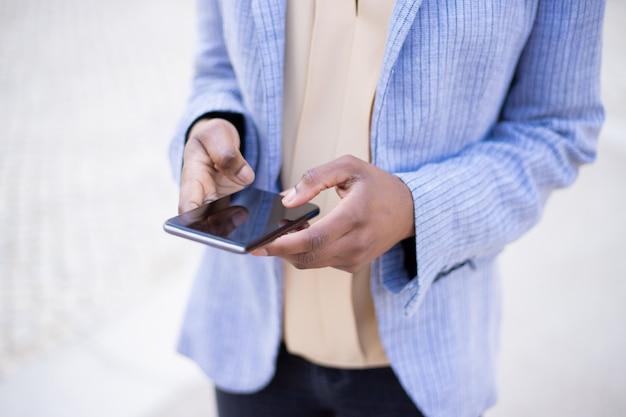Vista recortada de mensajes de mujer en el teléfono inteligente