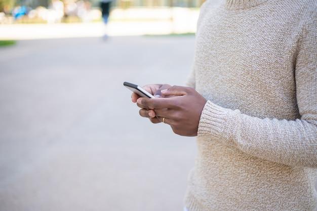 Vista recortada de mensajes de texto de mujer en smartphone