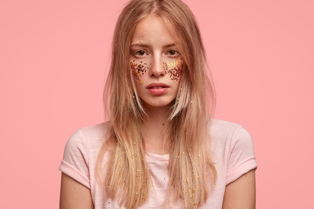 Vista recortada de una mujer hermosa que ha decorado las mejillas con destellos, se ve con confianza